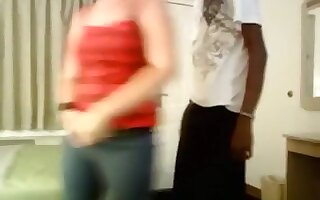 Redhead girl has sex with a skinny black guy in a motel, while a friend tapes it.